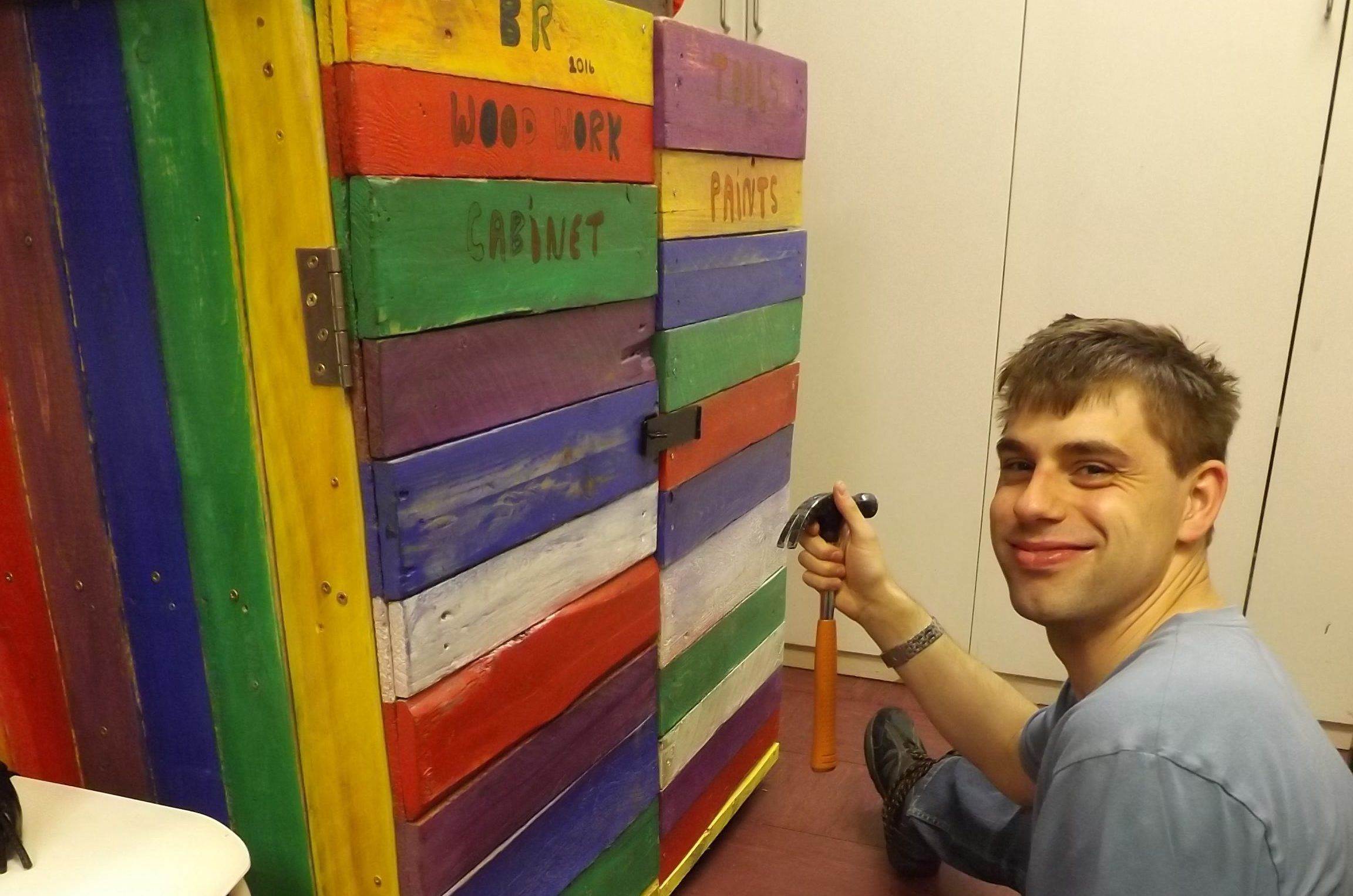 Man with learning disabilities kneeling down holding a hammer next to a cabinet