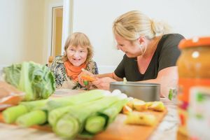 Two women preparing vegetables