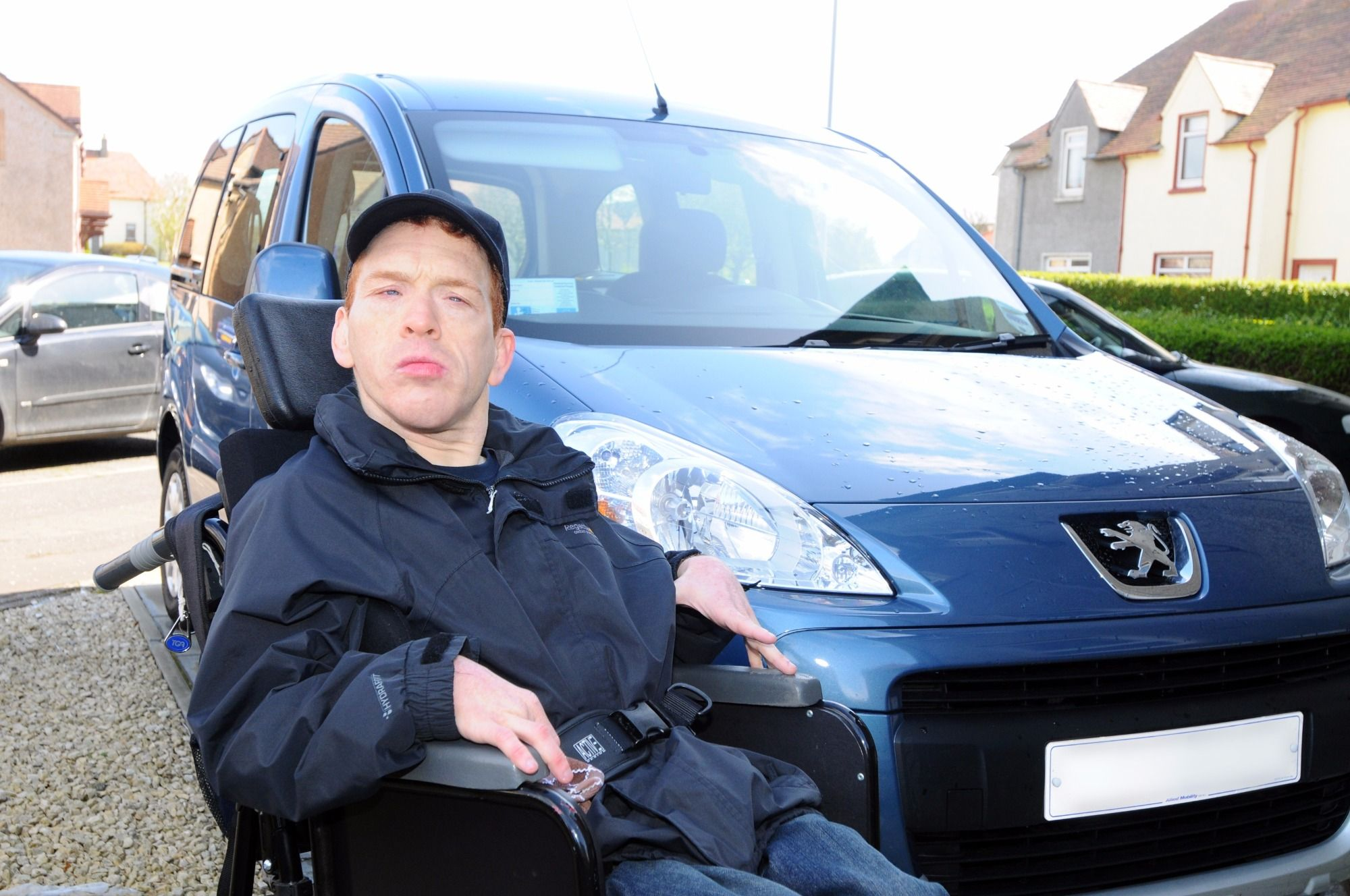 Man in wheelchair next to car