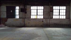 An empty warehouse with three windows