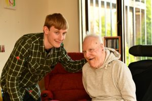 Young support worker with his hand on the shoulder of an older man with learning disabilities