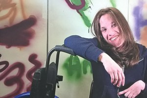 Woman sat next to her wheelchair with graffiti behind her