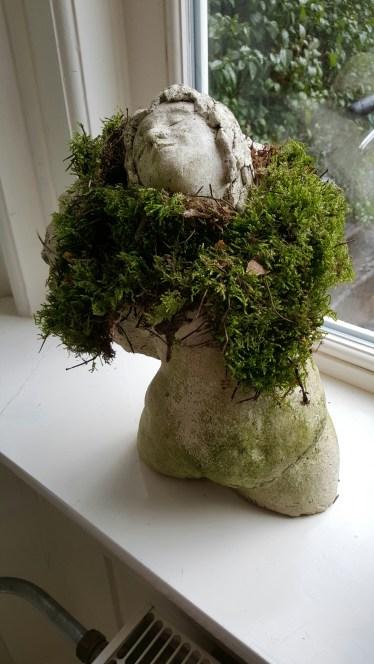 Engelsmens. Gipsen beeld met mos begroeid.