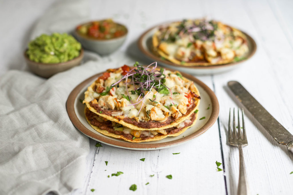 an easy, insanely delicious dinner idea for any weeknight. shredded chicken, creamy refried black beans, crispy tostada shells, and melty cheese make the ultimate tex-mex dinner idea! crunchy chicken tostada stacks | a flavor journal food blog