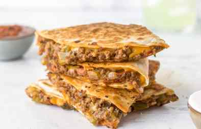 Cheesy ground beef quesadillas stacked on top of one another with salsa and a margarita in the background