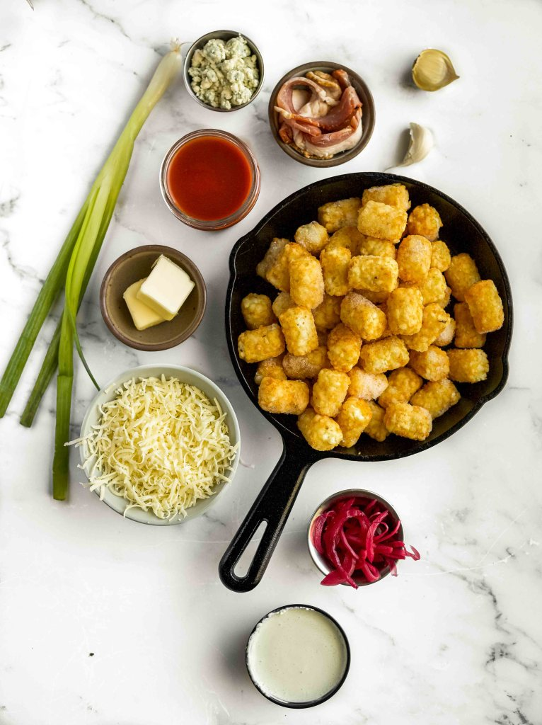 A photo of the ingredients needed to make buffalo tots: tater tots, butter, green onion, buffalo sauce, shredded cheese, bacon, pickled onions, blue cheese crumbles, and ranch dressing