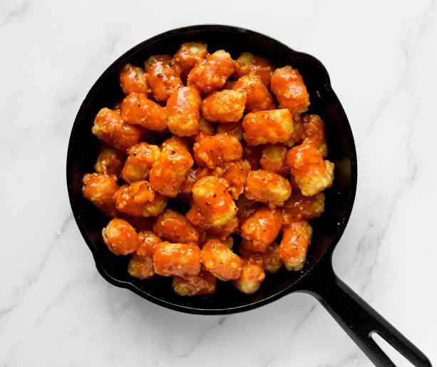 Crispy tater tots tossed in a garlicky buffalo sauce, placed inside a small cast iron pan.