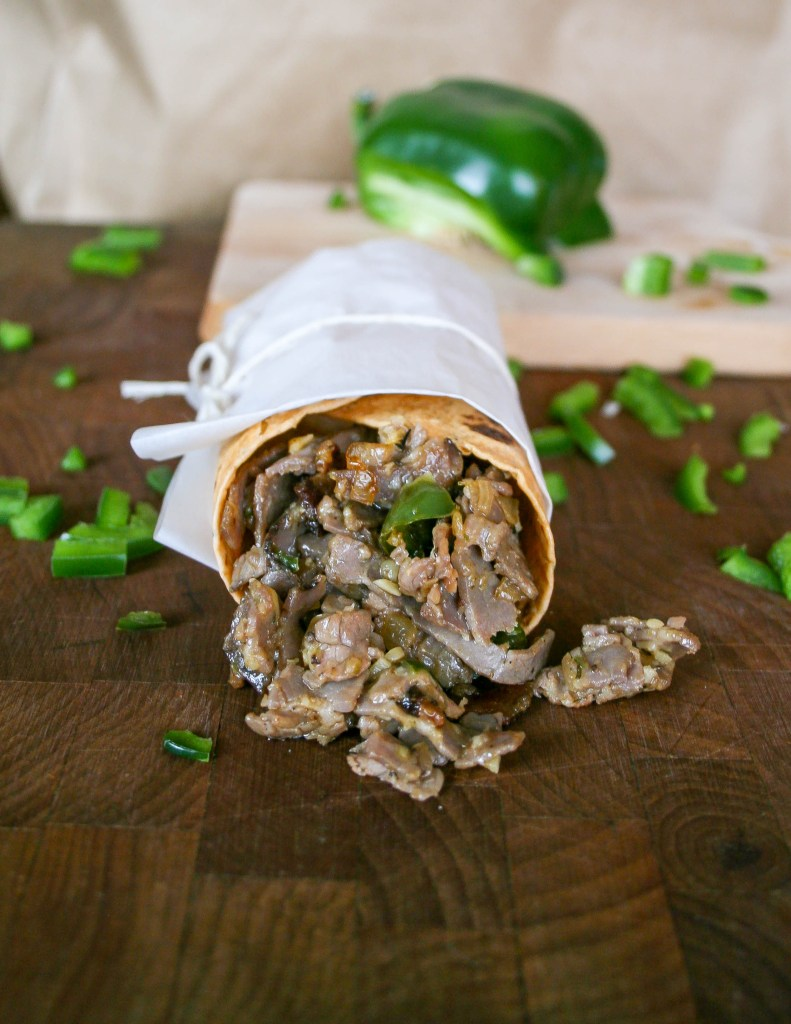 cajun spiced beef mixed with onion, green pepper, jalapeño, garlic, and melted cheese wrapped in a cheddar tortilla wrap and served hot! | spicy cajun philly cheesesteak wrap | a flavor journal food blog