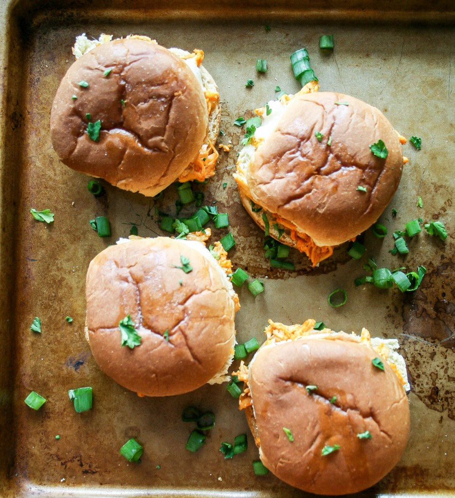 buffalo chicken sliders are made with shredded chicken, wing sauce, seasonings, cheese, and ranch dressing piled onto a slider bun and baked. they're easy, delicious, and perfect for any party! buffalo chicken sliders | a flavor journal