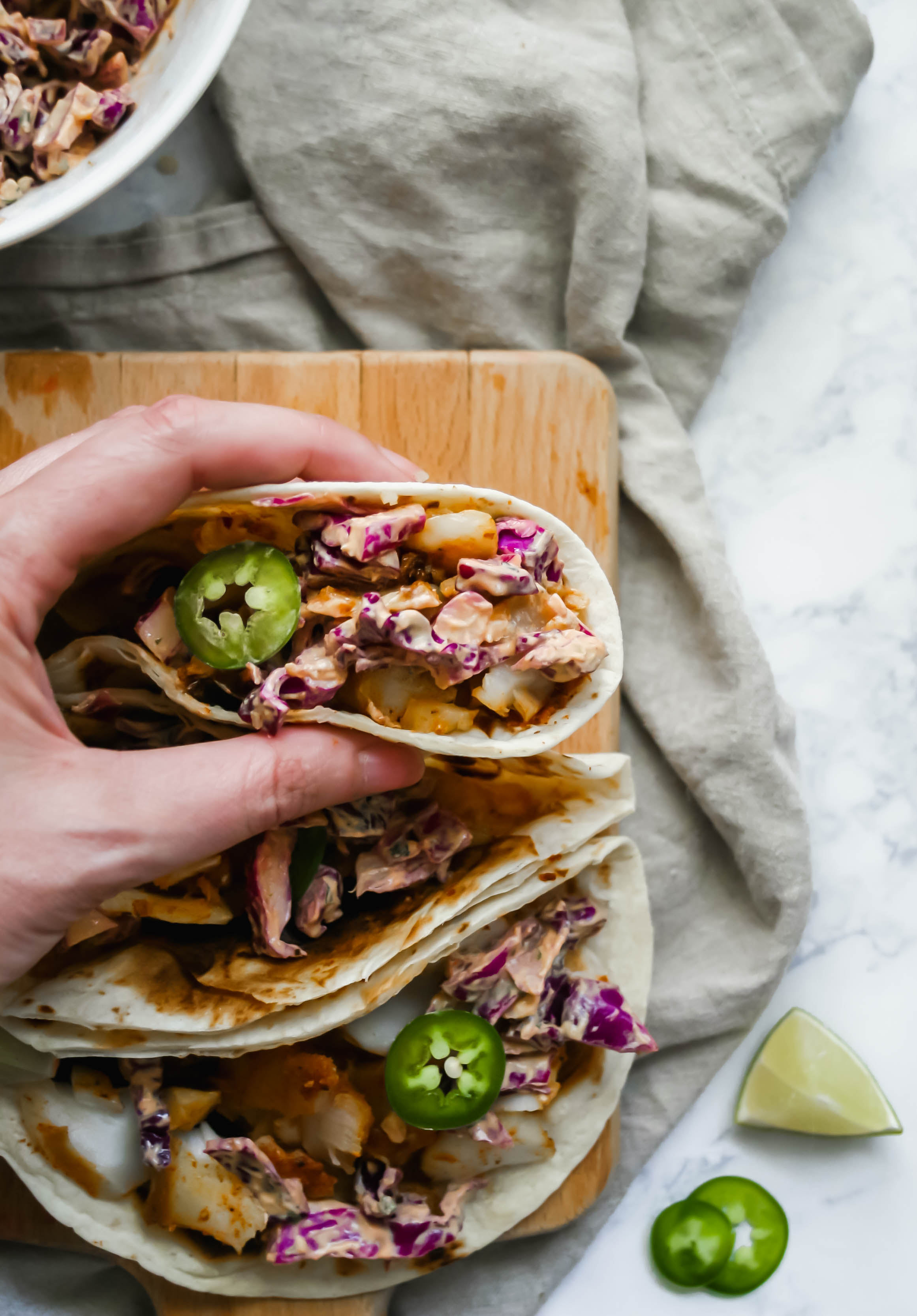 perfectly flaked white fish and crunchy red cabbage slaw are tossed in a cool and creamy sauce for easy and super delicious fish tacos. fish tacos with crunchy slaw | a flavor journal food blog