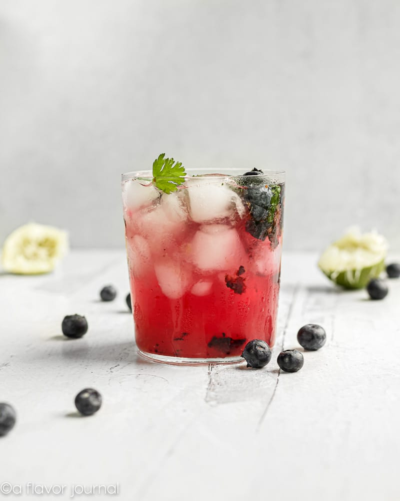 A cocktail glass full of crushed ice and vibrant blueberry cilantro margarita.