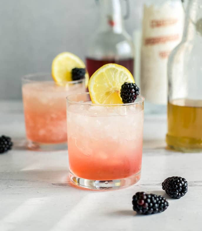 The blackberry bramble is an easy gin cocktail with blackberry liqueur, fresh lemon juice, simple syrup, and gin. Served in a short glass with crushed ice, then garnished with lemon and blackberry.