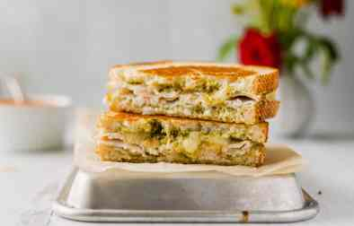 A grilled cheese sandwich made with pesto and turkey, cut in half and stacked on top of a small sheetpan lined with parchment paper