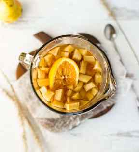 A flatlay photo of baked pear and apple sangria in a large glass pitcher.