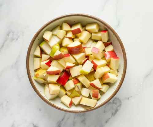 A bowl of apples and pears ready to be tossed with brown sugar for a baked pear and apple sangria.