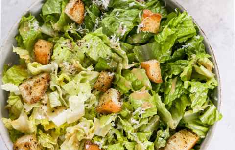 A bowl of Caesar salad with crunchy croutons and a small glass jar of Caesar dressing in the background.