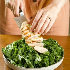 An action shot of sliced grilled chicken being plated on top of massaged kale.