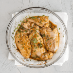 A glass bowl with chicken thighs and ingredients to make a cilantro lime and honey chicken marinade