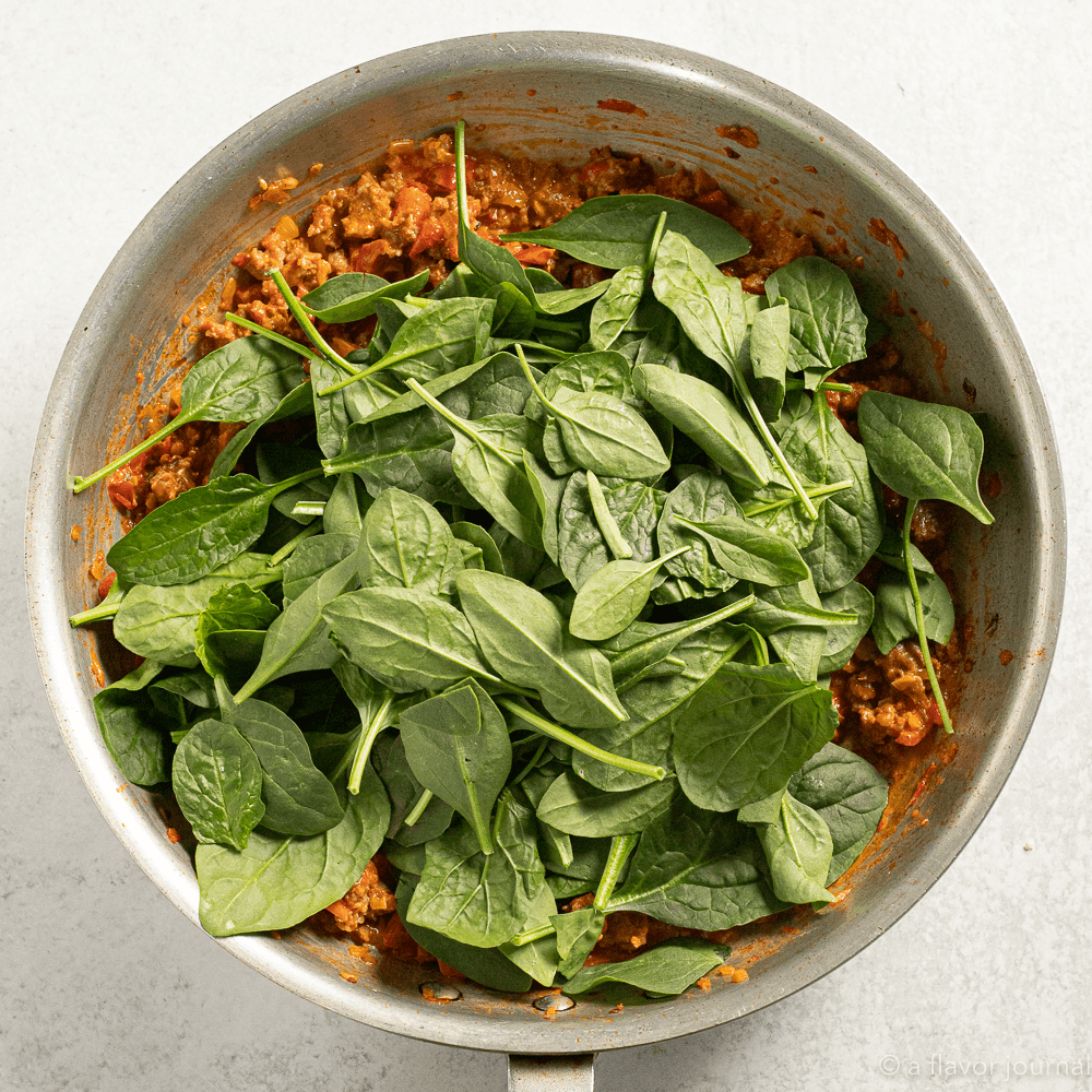 Process shot of cooking chorizo and tomato pasta with fresh spinach