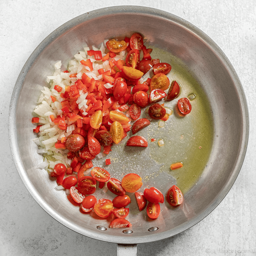 A skillet with oil, tomatoes, and onions