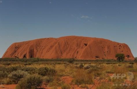 オーストラリア北部特別地域にある巨大な一枚岩、ウルル(別称エアーズロック)(2013年10月11日撮影)。(c)AFP/Greg Wood