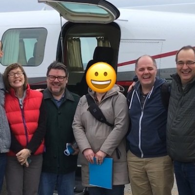 Six people, smiling beside an airplane after their graduation flight from Dr. Shulman's The Non Flyer treatment course.