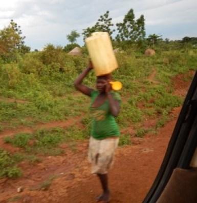水運ぶ女性 携帯電話片手に 裸足で