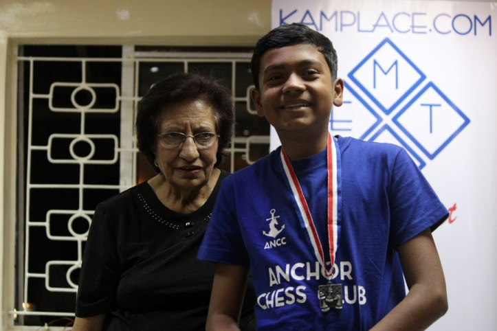 Sumit Deshpande of Anchor Chess Club receiving his medal for second place (Under 18) from Mrs Rahemtullah / Photo by Allan Rongoey