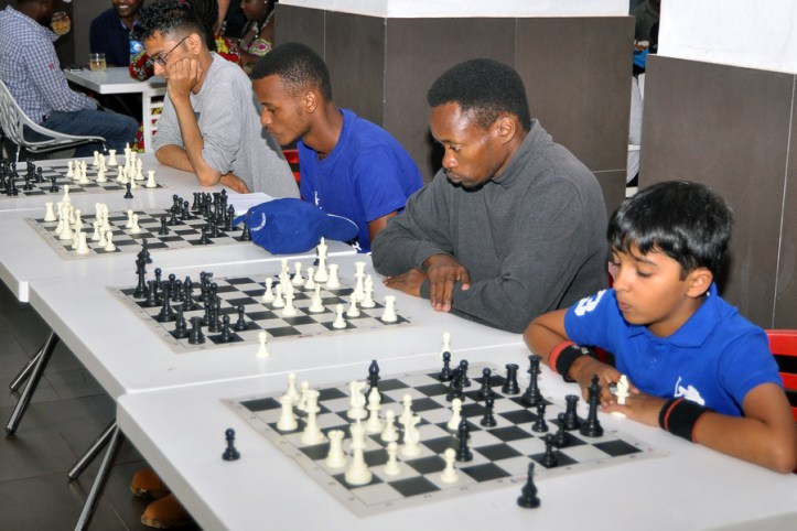 Members of Anchor Chess Club (Mukund Budhbhatti, Brian Waweru and Lalith Gantla) and Duncan Apiyo (in grey sweatshirt) ponder their next moves