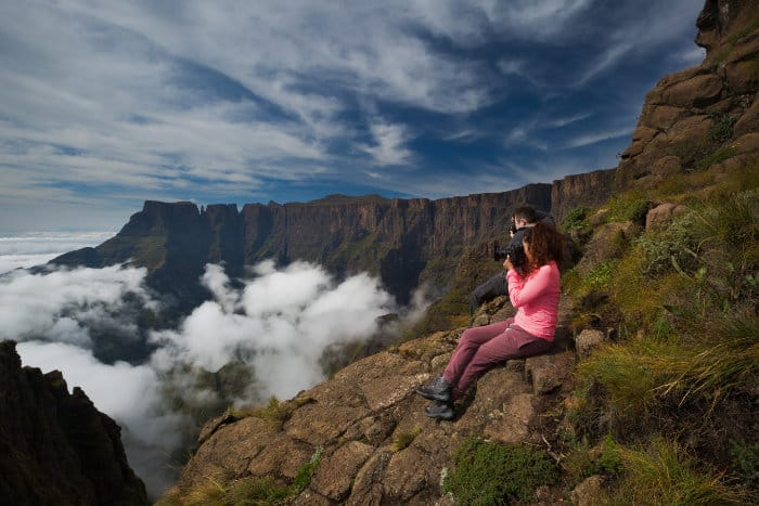 Two hikers take pictures of the Drakensberg Amphitheatre from Witches Viewpoint