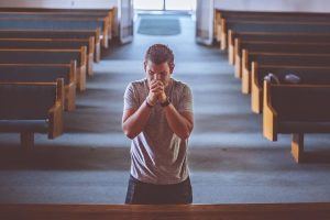 Photo of a man praying in an article about the bias against people of faith by dk on African American Conservatives