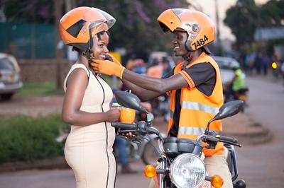 un conducteur mettant un casque à son client, Safe Boda appli,