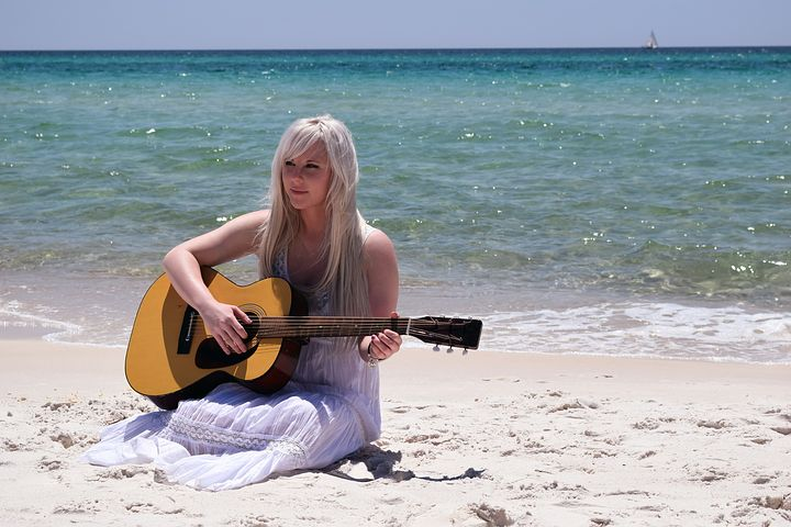A girl playing guitar at the beach