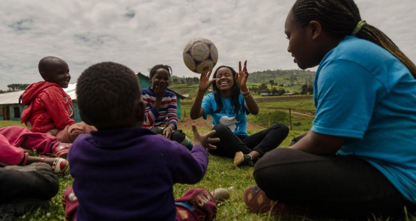 Sally Gacheru, center, tosses a ball to a child in Sakutiek, Kenya. Gacheru, who was born in Kenya but moved to St. Louis four years ago, was part of a service trip back home for fellow immigrant teens this month