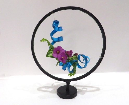 A miniature arrangement of African violet blossoms and blue curling wire suspended in a wrought iron stand
