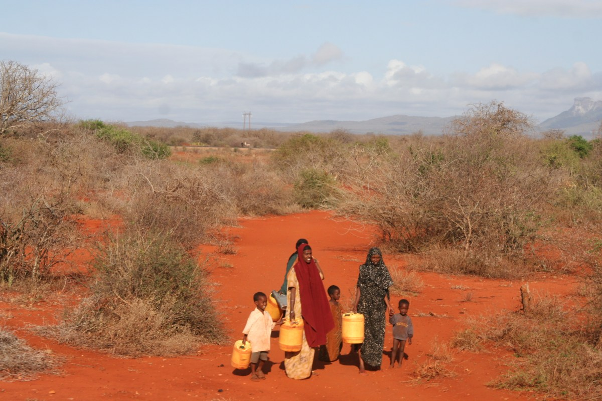 Kenyans going for water in Eastern Province with jerry cans on red dirt