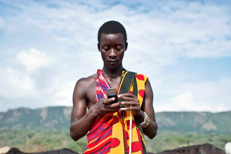 Young Masai male checks mobile device.