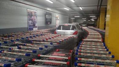 Man parks wrongly after which his car is enclosed by shopping trolleys