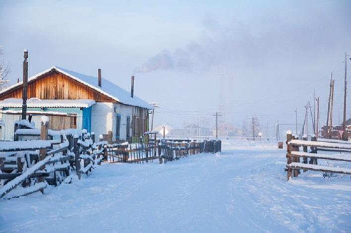 Oymyakon, Sakha Republic, Russia - February 22, 2020: Traditional wooden houses (izba) and smoke from the chimneys, one of the coldest permanently inhabited settlements on Earth, Pole of cold, -48 °C