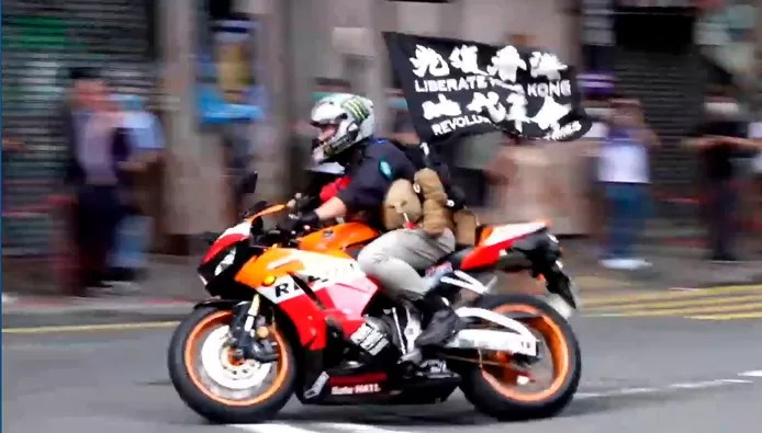 Screenshot from video showing Tong Ying-kit riding a motorcycle into three police officers on July 1, 2020, the day the national security law came into effect.