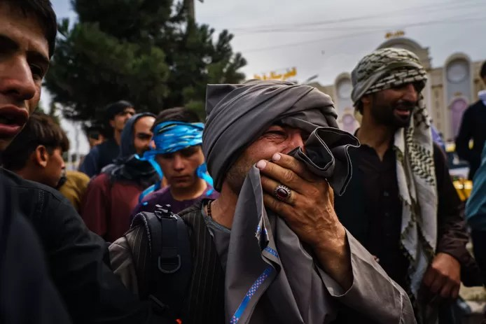 An Afghan man watches in horror as Taliban fighters use firearms, whips and sticks to attack the crowd near the international airport in Kabul