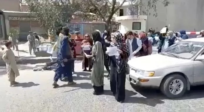 A still from a video shows an armed Taliban fighter stepping towards a group of protesting women