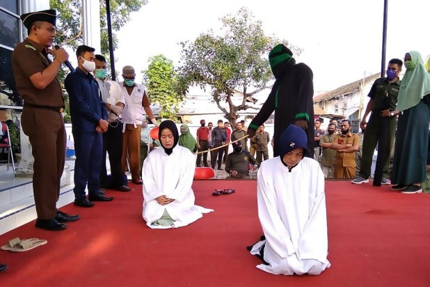Two Indonesian women are whipped 100 times each in public for online pimping (photos)