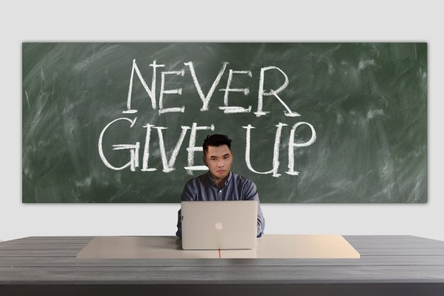 """An Asian man sitting behind a desk with a laptop with a blackboard behind him with """"Never Give Up"""" written on it"""