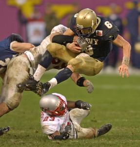 Navy quarterback Aaron Polanco jumps over a New Mexico player in the fourth quarter of Navy's 34-19 win in the 2004 Emerald Bowl. Polanco scored on runs of 14, 1 and 27 yards and completed a 61-yard touchdown pass in the win. (AP Photo/Paul Sakuma)