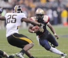 Navy quarterback Ricky Dobbs eludes a tackle against Missouri last year. (Navy photo)