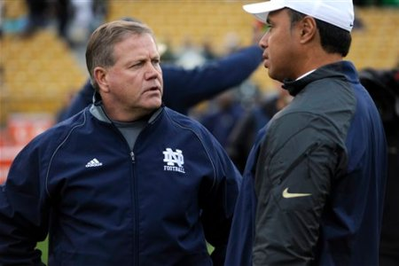 Notre Dame coach Brian Kelly talks with Navy coach Ken Niumatalolo prior to a in a NCAA college football game with BYU Saturday Nov. 23, 2013 in South Bend, Ind. (AP Photo/Joe Raymond)