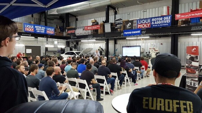 APR and Dinan dealers meet with LIQUI MOLY. The photo shows a group of people sitting in chairs, watching a presentation.