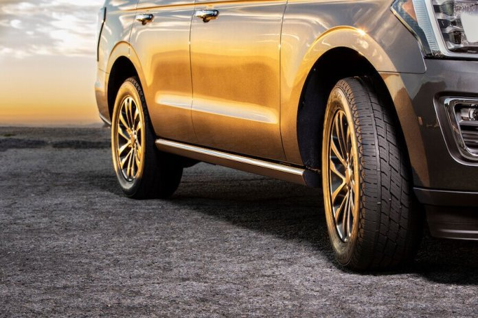 This image shows a close-up of the all-new Toyo Open Country H/T II tire on a silver-colored truck, in a photo taken from the front of the truck. The silver truck is glowing yellow and gold from the sunlight.