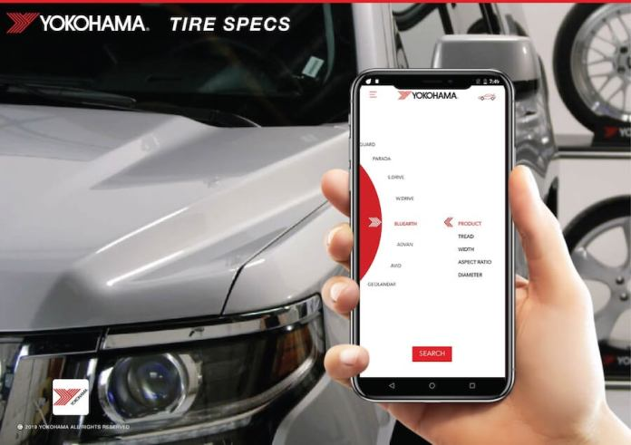 "This image shows someone holding a smartphone in their right hand. The Yokohama app is active. The person is scrolling through the language selection in the app. In the background is a silver vehicle. At the top of the image, it says ""Yokohama Tire Specs."""